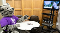 Tommie Mascot using a media viewing/listening room in OSF Library
